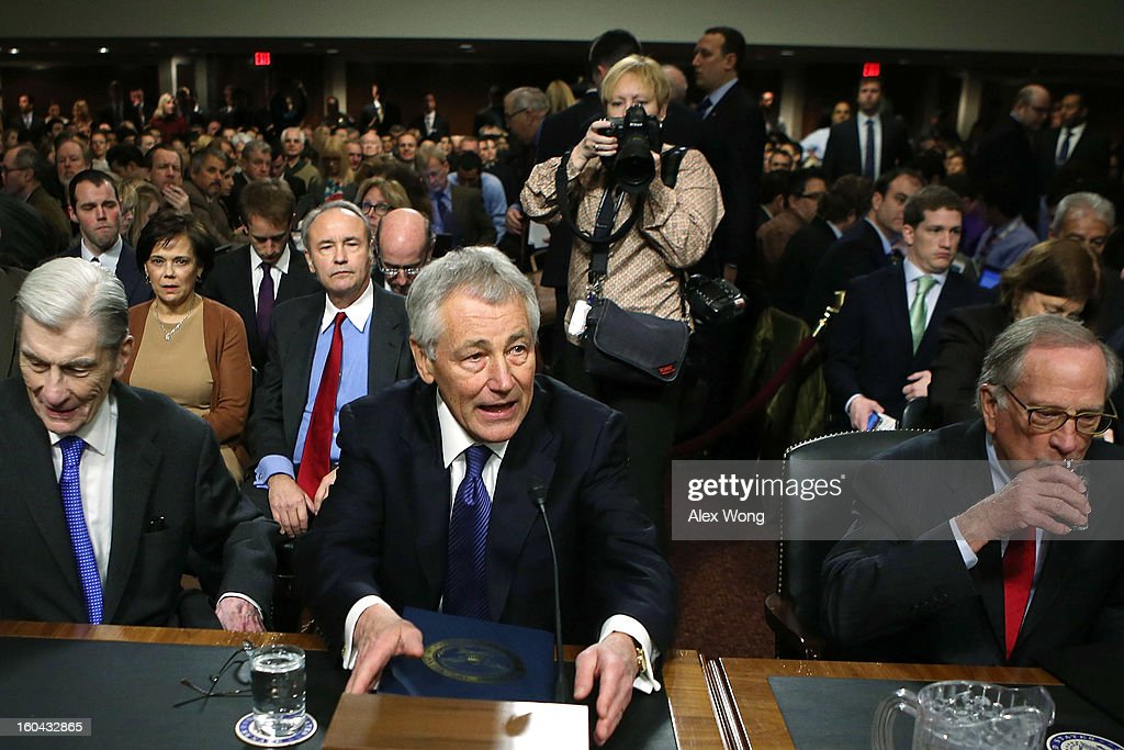 Former U.S. Sen. Chuck Hagel (R-NE) (C) takes his seat with former Sen. John Warner (R-VA) (L) and former Sen. Sam Nunn (D-GA) (R) as he arrives at his confirmation hearing to become the next secretary of defense before the Senate Armed Services Committee on Capitol Hill January 31, 2013 in Washington, DC. President Barack Obama nominated Hagel, a controversial choice as Hagel opposed former President George W. Bush and his own party on the Iraq War and upset liberals with his criticism of a gay ambassador, for which he later apologized.