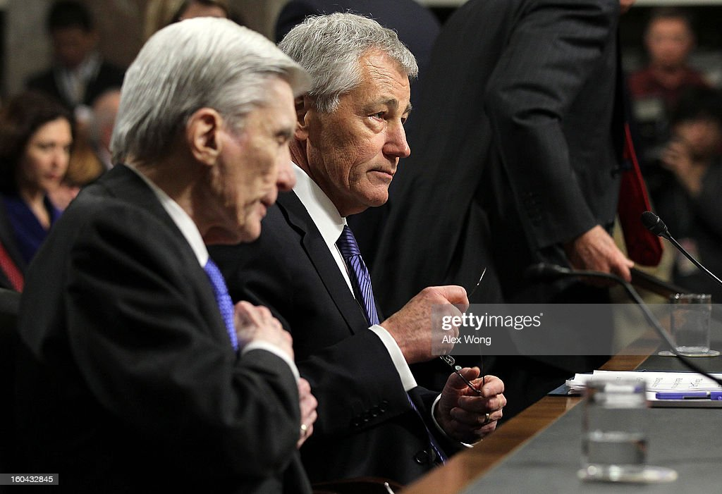 Former U.S. Sen. John Warner (R-VA) (L) and Sen. Chuck Hagel (R-NE) (R) during Hagel's confirmation hearing to become the next secretary of defense before the Senate Armed Services Committee on Capitol Hill January 31, 2013 in Washington, DC. President Barack Obama nominated Hagel, a controversial choice as Hagel opposed former President George W. Bush and his own party on the Iraq War and upset liberals with his criticism of a gay ambassador, for which he later apologized.