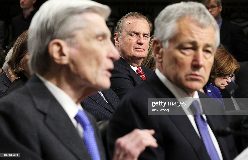 Former U.S. Sen. John Warner (R-VA) (L) speaks as Sen. Chuck Hagel (R-NE) (R) and former National Security Adviser General James Jones (C) look on during Hagel's confirmation hearing to become the next secretary of defense before the Senate Armed Services Committee on Capitol Hill January 31, 2013 in Washington, DC. President Barack Obama nominated Hagel, a controversial choice as Hagel opposed former President George W. Bush and his own party on the Iraq War and upset liberals with his criticism of a gay ambassador, for which he later apologized.