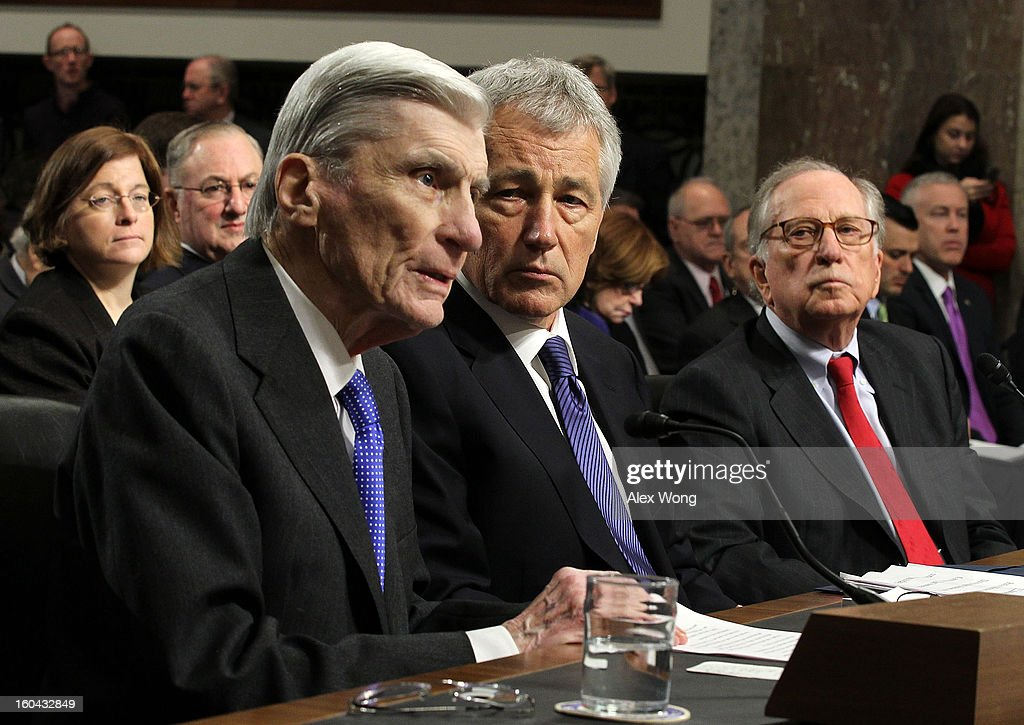 Former U.S. Sen. John Warner (R-VA) (L) speaks as Sen. <a gi-track='captionPersonalityLinkClicked' href=/galleries/search?phrase=Chuck+Hagel&family=editorial&specificpeople=504963 ng-click='$event.stopPropagation()'>Chuck Hagel</a> (R-NE) (2nd L) and former Sen. Sam Nunn (D-GA) (R) look on during Hagel's confirmation hearing to become the next secretary of defense before the Senate Armed Services Committee on Capitol Hill January 31, 2013 in Washington, DC. President Barack Obama nominated Hagel, a controversial choice as Hagel opposed former President George W. Bush and his own party on the Iraq War and upset liberals with his criticism of a gay ambassador, for which he later apologized.