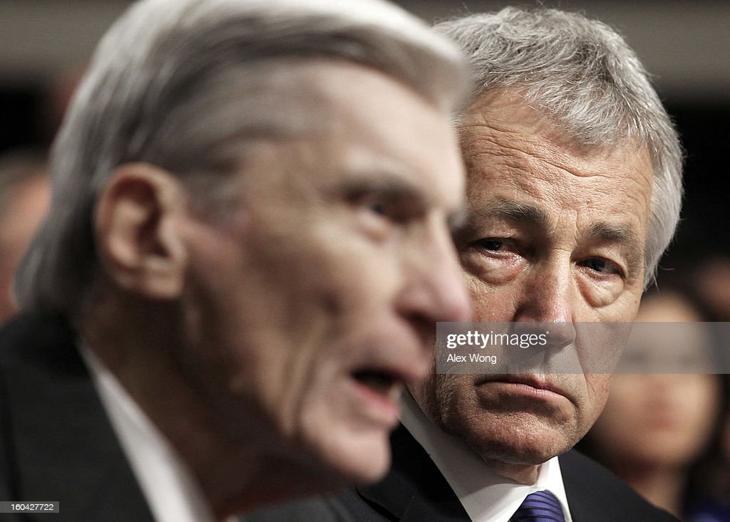 Former U.S. Sen. John Warner (R-VA) (L) speaks as Sen. Chuck Hagel (R-NE) (R) looks on during Hagel's confirmation hearing to become the next secretary of defense before the Senate Armed Services Committee on Capitol Hill January 31, 2013 in Washington, DC. President Barack Obama nominated Hagel, a controversial choice as Hagel opposed former President George W. Bush and his own party on the Iraq War and upset liberals with his criticism of a gay ambassador, for which he later apologized.