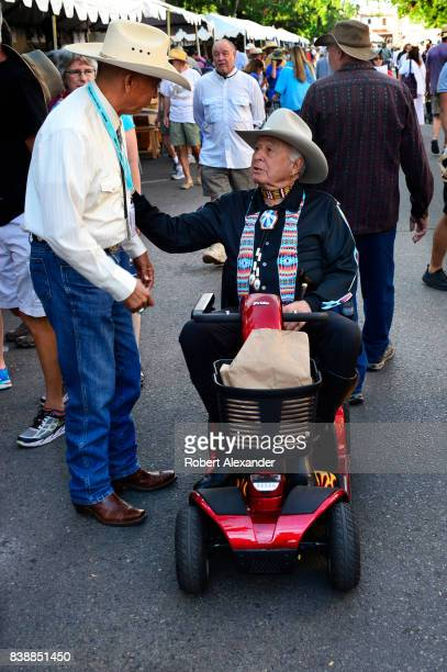 Former US Senator Ben Nighthorse Campbell pauses to talk with Navajo artist Rick Nez at the Santa Fe Indian Market in Santa Fe New Mexico The annual...