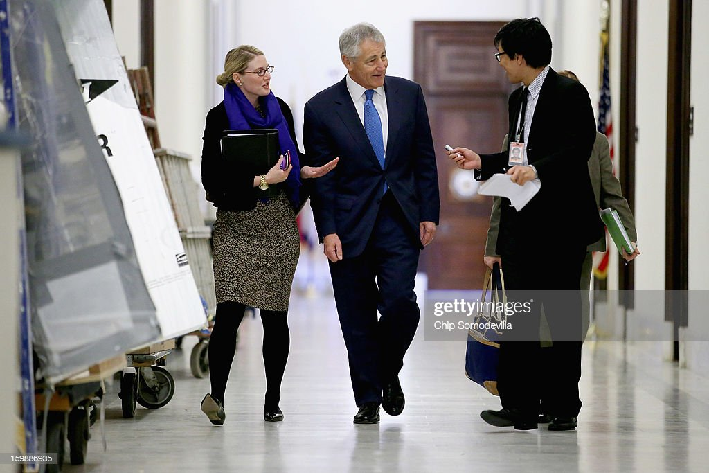 Former U.S. Senator Chuck Hagel (C) is quesitoned by a reporter as he walks down the hallway of the Russell Senate Office Building with CIA Spokesperson Marie Harf (L) before meeting with Sen. John McCain (R-AZ) on Capitol Hill January 22, 2013 in Washington, DC. Hagel, who cochaired McCain's 2000 presidential campaign, has been nominated by U.S. President Barack Obama to succeed Leon Panetta as Secretary of Defense.