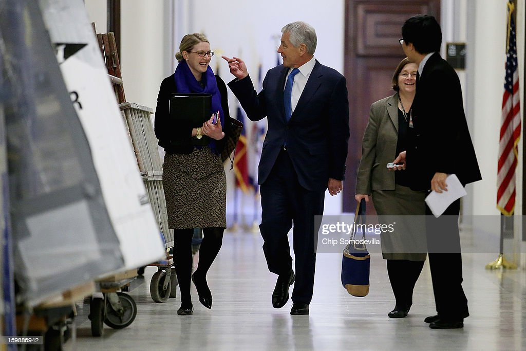 Former U.S. Senator Chuck Hagel (C) walks down the hallway of the Russell Senate Office Building with CIA Spokesperson Marie Harf (L) and Assistant Secretary of Defense for Legislative Affairs Elizabeth King before meeting with Sen. John McCain (R-AZ) on Capitol Hill January 22, 2013 in Washington, DC. Hagel, who cochaired McCain's 2000 presidential campaign, has been nominated by U.S. President Barack Obama to succeed Leon Panetta as Secretary of Defense.