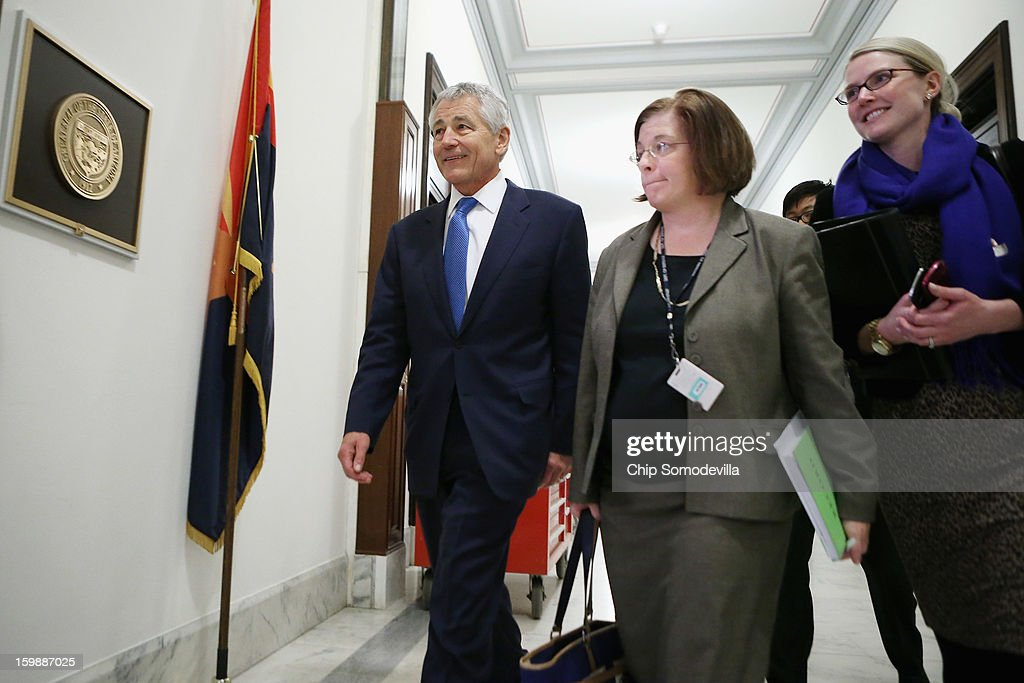 Former U.S. Senator Chuck Hagel (L) walks down the hallway of the Russell Senate Office Building with CIA Spokesperson Marie Harf (R) and Assistant Secretary of Defense for Legislative Affairs Elizabeth King before meeting with Sen. John McCain (R-AZ) on Capitol Hill January 22, 2013 in Washington, DC. Hagel, who cochaired McCain's 2000 presidential campaign, has been nominated by U.S. President Barack Obama to succeed Leon Panetta as Secretary of Defense.