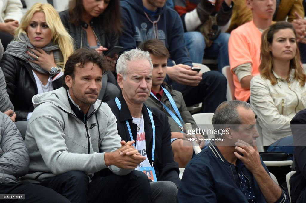 Former US tennis player John McEnroe (2nd L) attends the men's fourth round match between Canada's Milos Raonic and Spain's Albert Ramos-Vinolas at the Roland Garros 2016 French Tennis Open in Paris on May 29, 2016. / AFP / Eric FEFERBERG