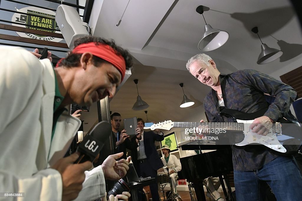 Former US tennis player John McEnroe (R) plays guitar next to French comedian and television commentator Cyrille Eldin during an event in Paris on May 27, 2016 organised by the 'We Are Tennis Fan Academy 2016' to train fans before they attend matches at the Roland Garros 2016 French Tennis Open. / AFP / MIGUEL