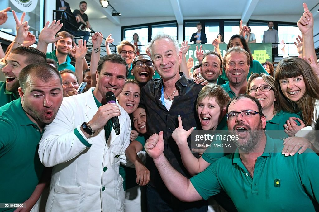 Former US tennis player John McEnroe (C) poses with fans at an event in Paris on May 27, 2016 organised by the 'We Are Tennis Fan Academy 2016' to train fans before they attend matches at the Roland Garros 2016 French Tennis Open. / AFP / MIGUEL