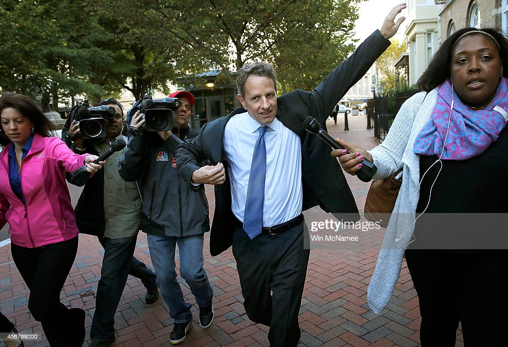 Former US Treasury Secretary Timothy Geithner puts on his suit jacket as he walks to the US Court of Federal Claims October 7 2014 in Washington DC...