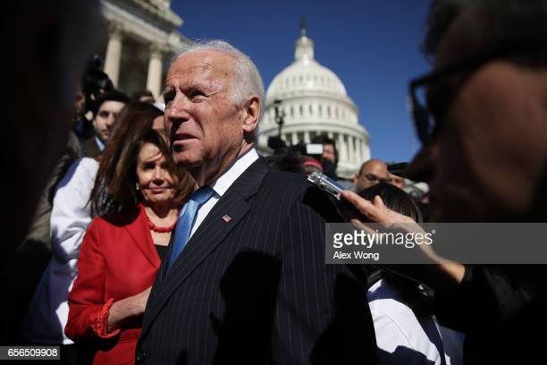 Former US Vice President Joseph Biden speaks to members of the media as House Minority Leader Rep Nancy Pelosi looks on after an event on health care...