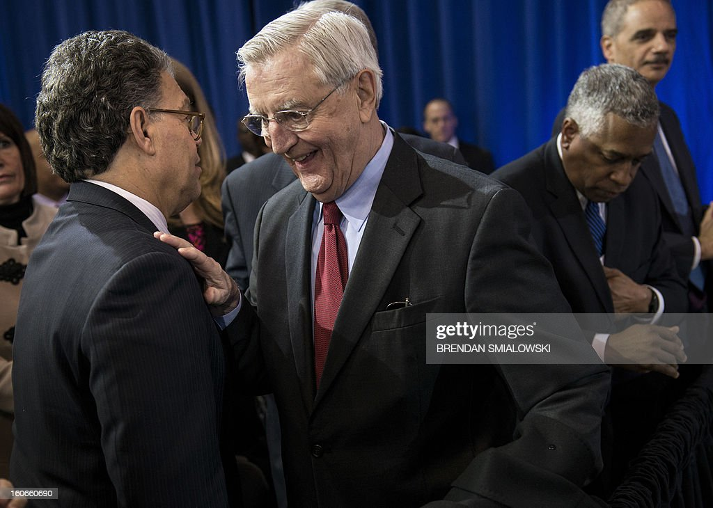 Former US vice president Walter Mondale (C) greets Democratic Senator from Minnesota Al Franken (L) while waiting for US President Barack Obama to speak about gun violence at the Minneapolis Police Department's special operations center on February 4, 2013 in Minneapolis, Minnesota. Obama spoke after meeting with local leaders and law enforcement to discuss gun violence and local efforts to control it. AFP PHOTO/Brendan SMIALOWSKI