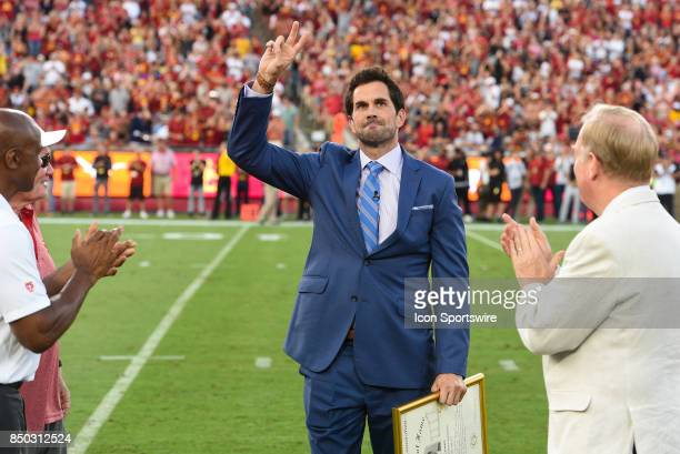 Former USC Trojan quarterback Matt Leinart salutes the crowd after being honored as a member of the College Football Hall of Fame during a college...