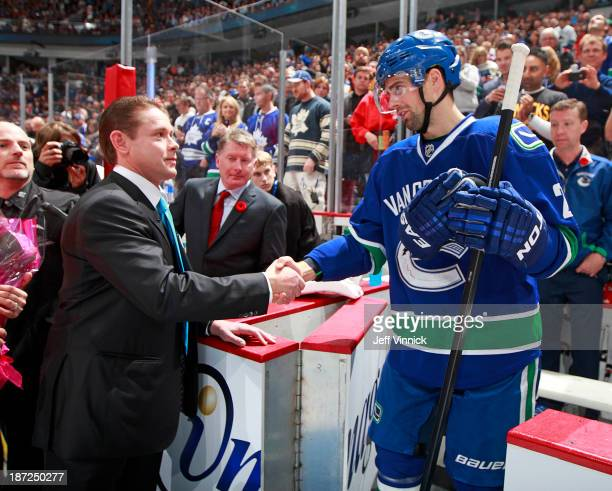 Former Vancouver Canuck Pavel Bure shakes hands with Dan Hamhuis of the Vancouver Canucks during his banner raising ceremony before the Vancouver...