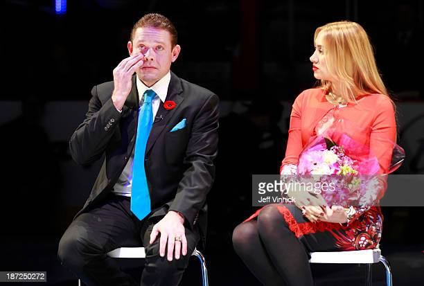 Former Vancouver Canuck Pavel Bure wipes his eye as he sits beside his wife Alina Khasanova during his banner raising ceremony before the Vancouver...