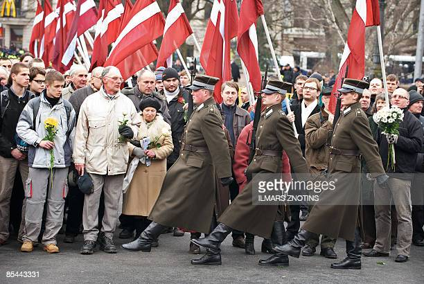 Former veterans of the Latvian Legion a force that was part of the Nazi German Waffen SS and their relatives look at an honour guard walking to the...