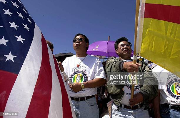 Former Vietnamese refugees Ky Nguyen and Richard Bui Jr carry US and the Vietnamese flag during a ceremony for the first Vietnamese refugees to...