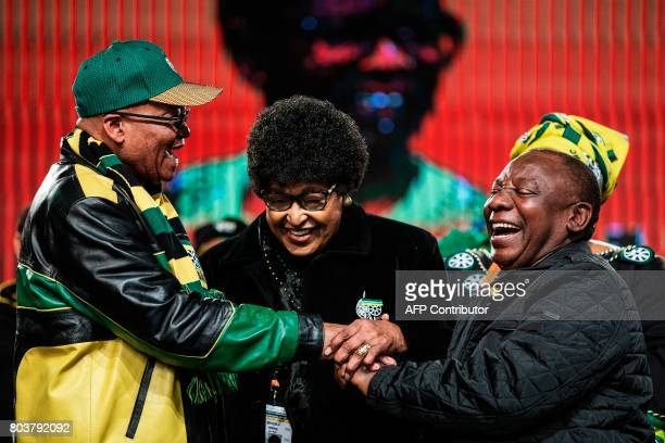 Former wife of the late South African President Nelson Mandela Winnie Mandela holds the hands of South African President Jacob Zuma and South African...