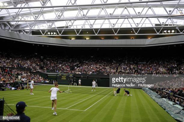 Former Wimbledon champion Steffi Graf in action with her partner and husband Andre Agassi in action against Great Britain's Tim Henman and Kim...