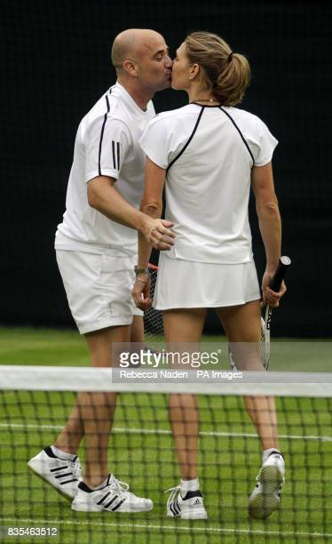 Former Wimbledon champion Steffi Graf kisses her husband and partner Andre Agassi at the end of an exhibition match against Great Britain's Tim...