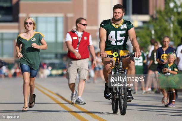 Former Wisconsin Badger and current Green Bay Packers linebacker Vince Biegel rides a bike to Packers training camp at Ray Nitschke Field on July...