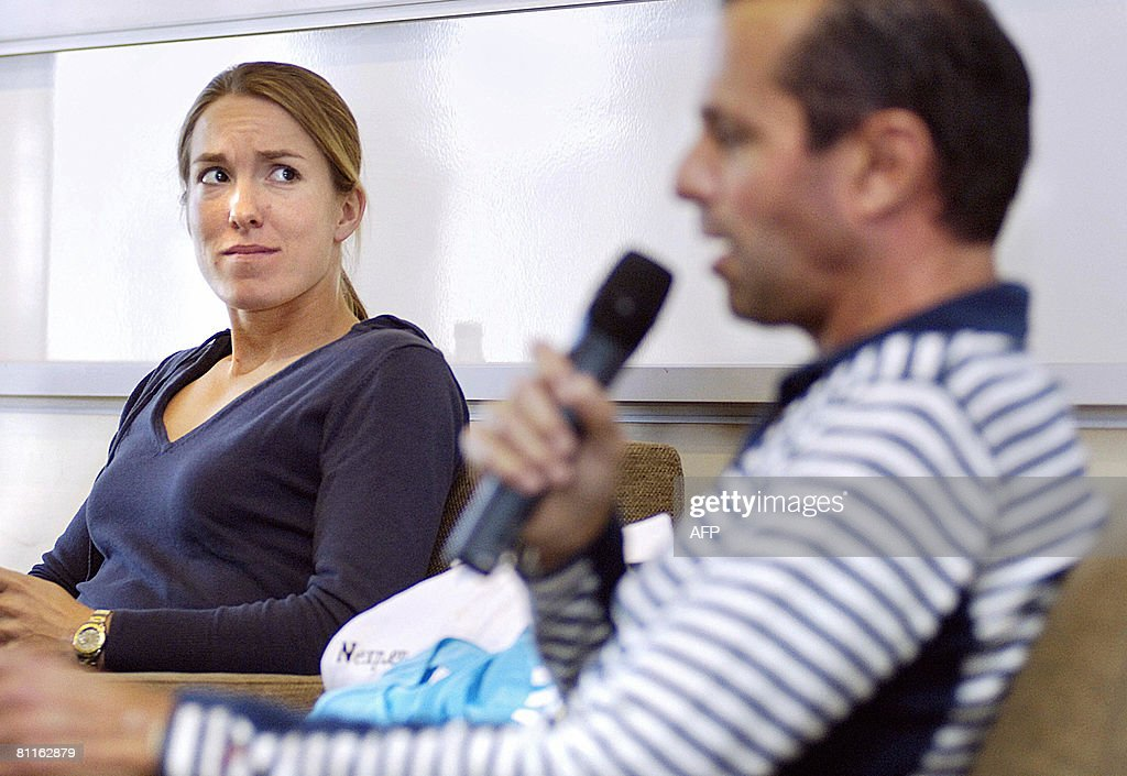 Former women's world number one Justine Henin listens to Tennis coach Carlos Rodriguez speaking as they present the workshop 'Management and coaching...