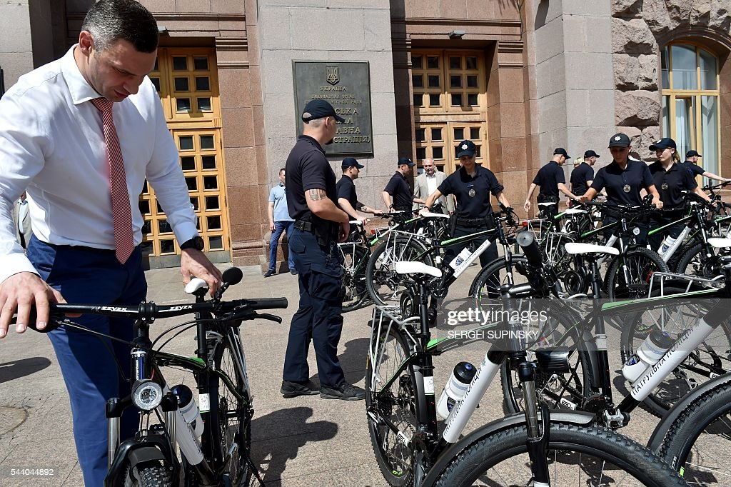 Former World Boxing Champion, Kiev Mayor Vitali Klitschko (L) looks at a bicycle during a ceremony to present bicycles to the Kiev police, in front of city hall of Kiev on July 1, 2016. Klitschko handed over 100 bicycles to the Kiev police for patrolling the Ukrainian capital. / AFP / SERGEI