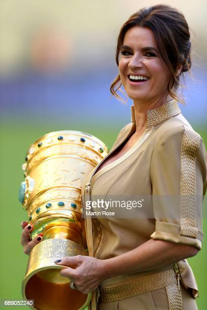 Former world class figure skater Katharina Witt walks on the pitch with the DFB Cup trophy prior to the DFB Cup final match between Eintracht...