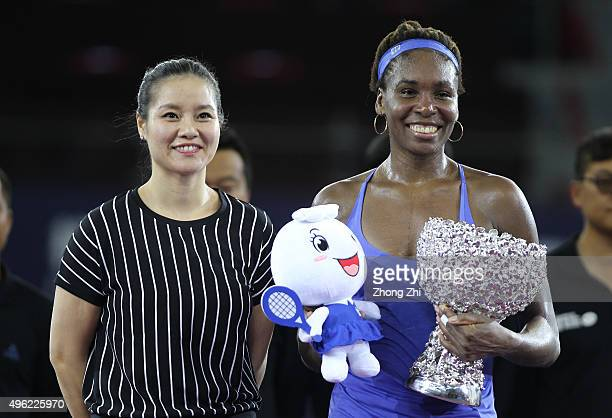 Former WTA player Li Na presents a gift to Venus Williams of USA along with the trophy after winning the final match against Karolina Pliskova of...