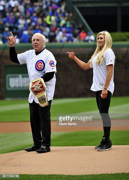 Former WWE champion Ric Flair and current women's champion Charlotte Flair throw out the ceremonial first pitch before the game between the Chicago...
