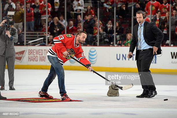 Former WWE wrestler CM Punk shoots the puck in between periods of the NHL game between the Los Angeles Kings and the Chicago Blackhawks at the United...