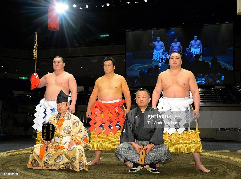 Former yokozuna sumo grand champion Chiyonofuji now stablemaster Kokonoe poses for photographs with Mongolian yokozunas Hakuho as the 'Tachimochi'...