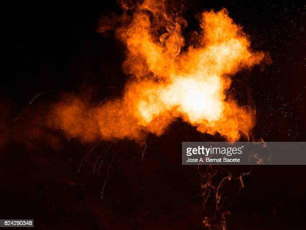 Forms and textures of an explosion of a powder of colors red an yellow on a black background