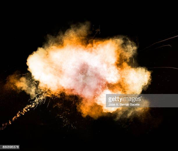 Forms and textures of an explosion of a powder of colors red an orange on a black background