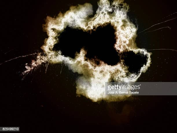 Forms and textures of an explosion of a powder of colors yellow an white on a black background
