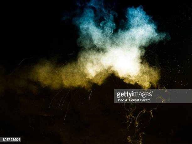 Forms and textures of an explosion of a powder of colors yellow an blue on a black background