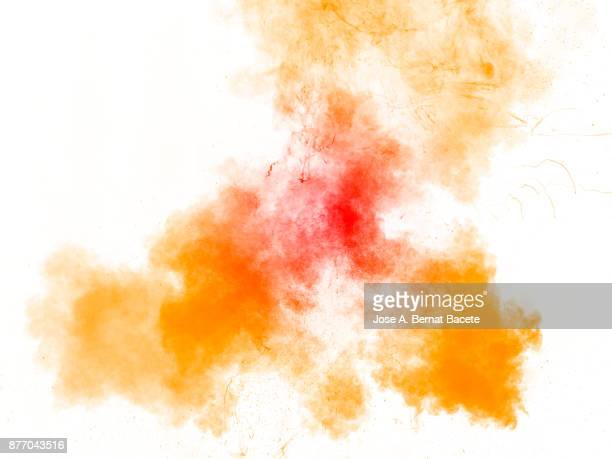 Forms and textures of an explosion of a powder of yellow and orange color on a  white background