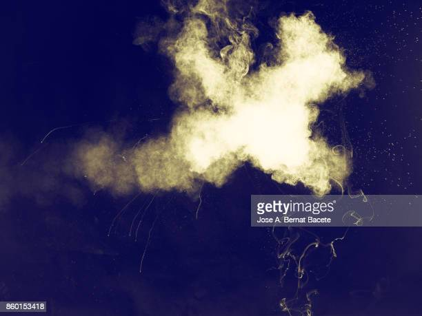 Forms and textures of an explosion of a powder of yellow color on a  black background