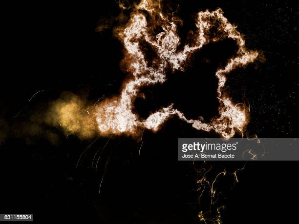 Forms and textures of an explosion of  powder in the form of a cloud of colors orange and yellow on a black background
