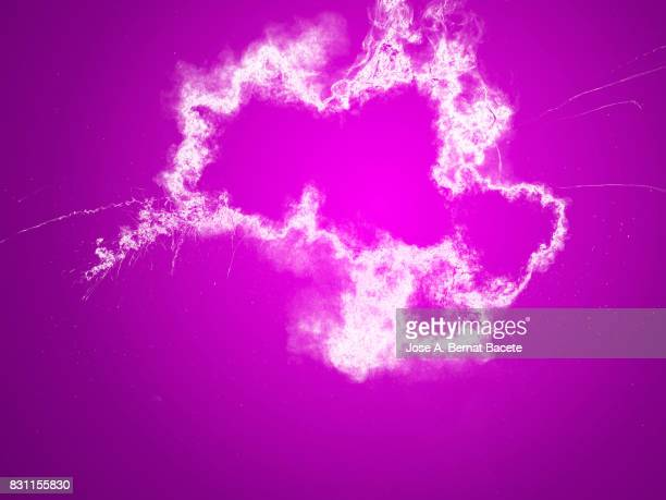 Forms and textures of an explosion of  powder in the form of a cloud of color white on a pink background