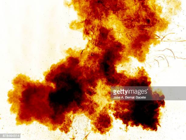 Forms and textures of an explosion of smoke and powder of yellow and orange color on a  white background