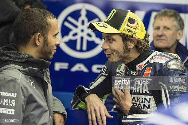 Formula 1 driver Lewis Hamilton of Great Britain speaks with Valentino Rossi of Italy and Yamaha Factory Racing before the MotoGP race during the...