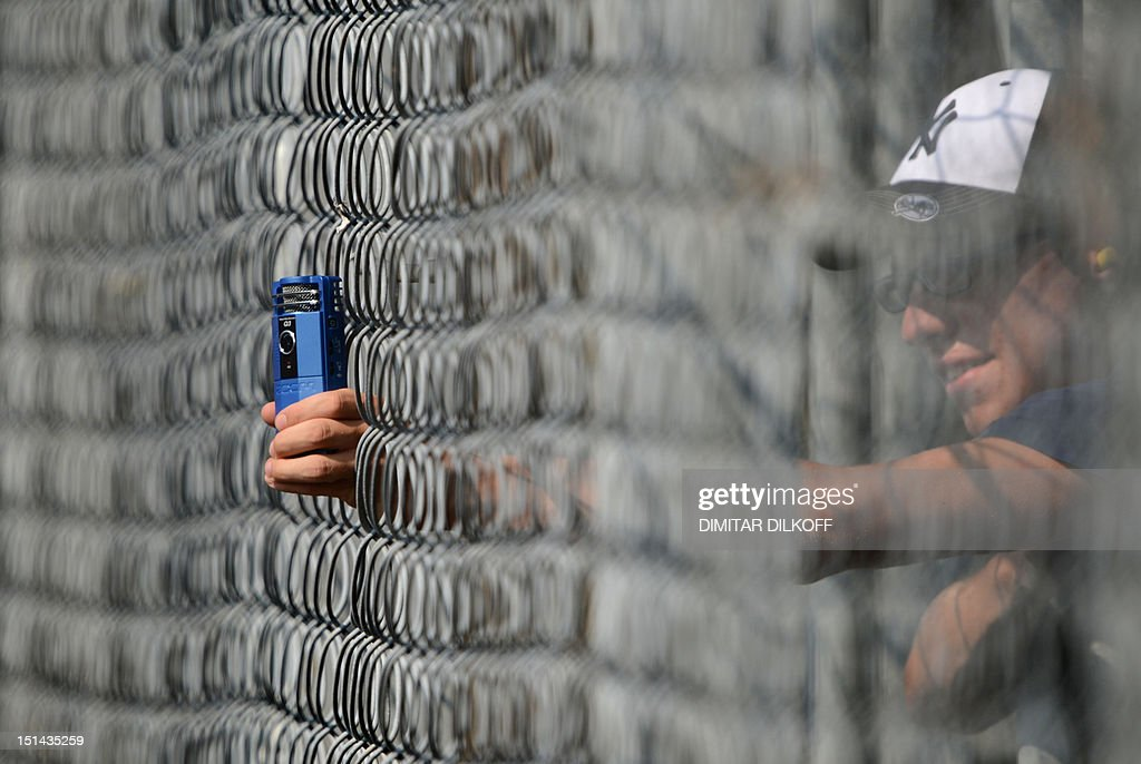 A formula 1 fan takes phictures with a mobile phone through a fence during the second practice session at the Autodromo Nazionale circuit on September 7, 2012 in Monza ahead of the Formula One Italian Grand Prix.