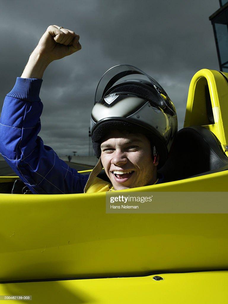 Formula 1 race car driver raising arm in victory, portrait : Stock Photo