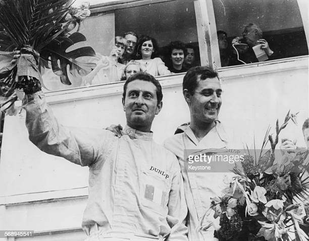 Formula 1 racing drivers Nino Vaccarella and Jean Guichet holding flowers and acknowledging the crowd after winning the famous Le Mans 24 Hour Race...