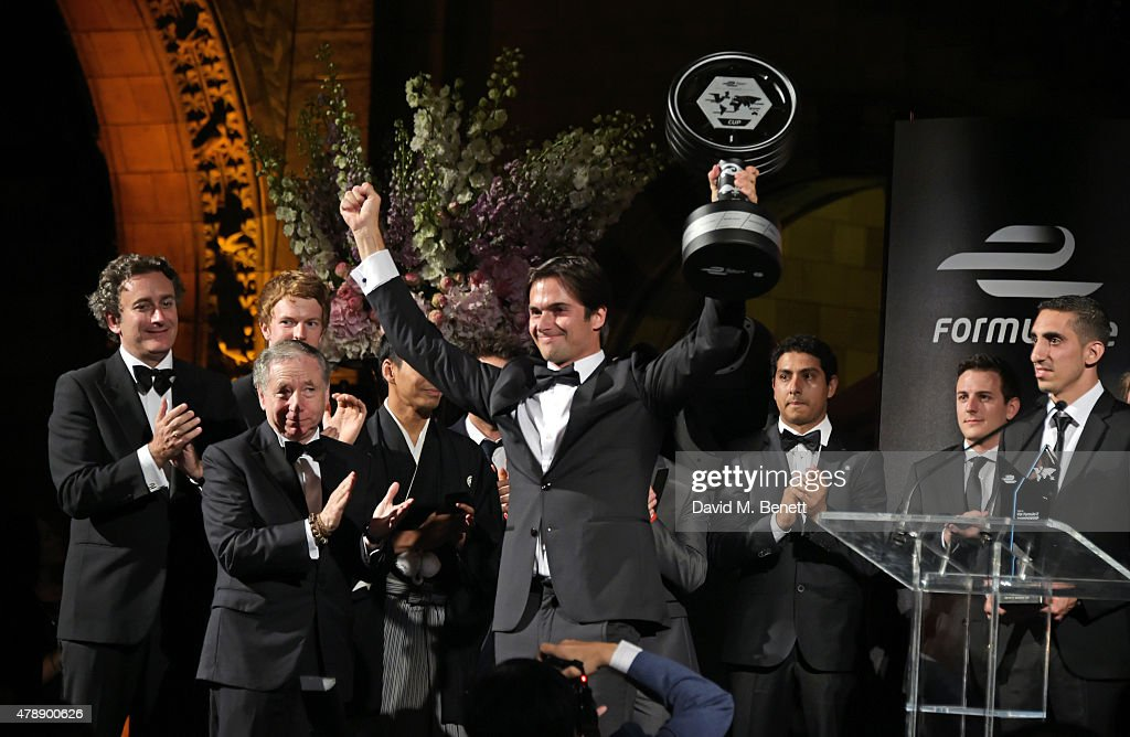 Formula E Championships winner Nelson Piquet Jr (C) celebrates his win on stage at the 2015 FIA Formula E Visa London ePrix Gala Dinner at the Natural History Museum on June 28, 2015 in London, England.