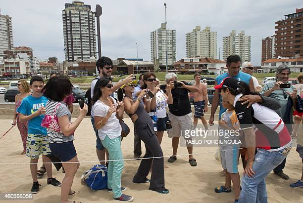 Formula E Mahindra Racing's driver Bruno Senna poses for Brazilian tourists before the official picture at Brava beach in Punta del Este resort some...