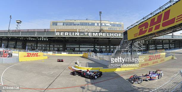Formula E pilots drive past the building of the former Tempelhof airport during a practise session of the 2015 Fia Formula E Berlin championships in...