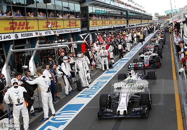 Formula One cars are lined up in the pit lane after the race was temporarily suspended following a crash between McLaren Honda's Spanish driver...