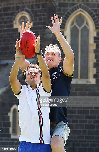 Formula One driver Felipe Massa marks a football against AFL player Joel Selwood at Melbourne Grammar on March 11 2015 in Melbourne Australia