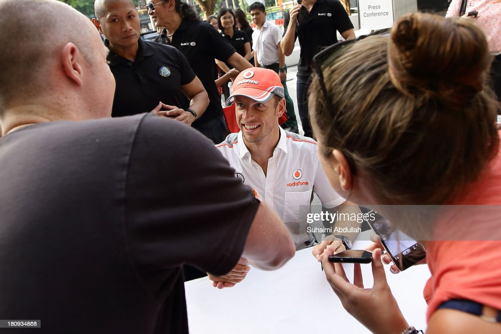 Formula One driver <a gi-track='captionPersonalityLinkClicked' href=/galleries/search?phrase=Jenson+Button&family=editorial&specificpeople=171505 ng-click='$event.stopPropagation()'>Jenson Button</a> of Great Britain and McLaren (C) greets fans and signs autographs during 'The One Legacy Tour' at ION Orchard on September 18, 2013 in Singapore.